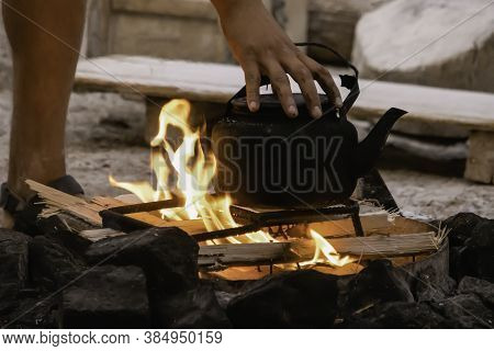 A Person's Hand Balancing A Soot Blackened Kettle Over A Campfire.