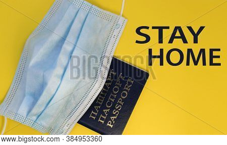 Passport Under A Disposable Medical Mask On A Yellow Background Close-up. Next To Your Passport, The