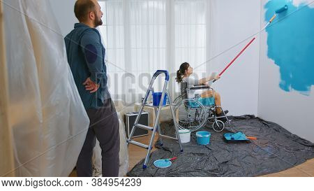 Paralyzed Woman Painting Wall With Roller Brush Sitting On Wheelchair. Handicapped, Disabled Ill And