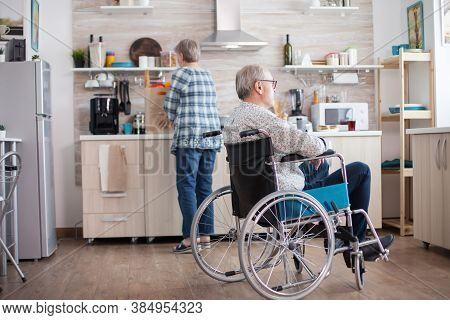 Pensive Disabled Elderly Person In Wheelchair Looking On The Window From The Kitchen. Disabled Man S