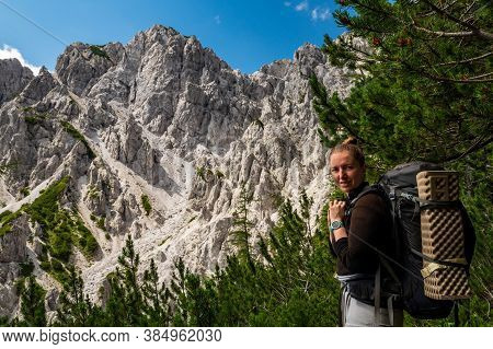 Young Woman Summer Hiker With Backpack And Smartwatch In Front Of Huge Limestone Rock Wall Before Hi