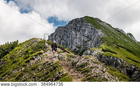 Young Woman Summerhiker En Face With Backpack Climbingsteep Slopes, Panoramic Peaks Andmountains