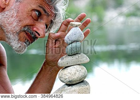 Happy Man Doing Stone Piles Along The River