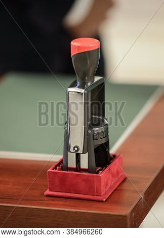 Shallow Depth Of Field Image With An Official Stamper On A Wooden Table