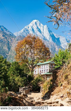 Traditional Nepalese Guesthouse With Mount Numbur On The Way To Nurning. Trekking In Nepal Himalayas