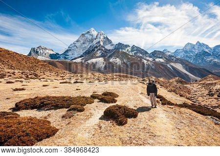 Young Woman Trekking In Valley Leading To The Everest Base Camp With Ama Dablam Peak. Trekking In Ne