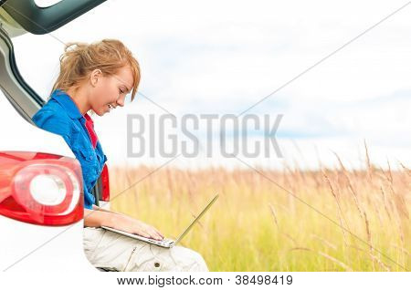 Woman In Meadow Near Car Working On Laptop.