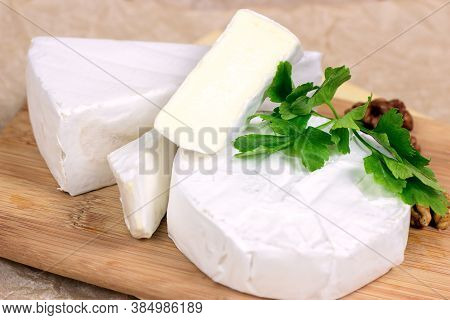 Slices And Circles Of Camembert And Brie Cheese With White Mold On Wooden Board Background.