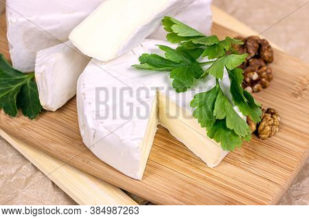 Slices And Circles Of Camembert And Brie Cheese With White Mold On A Light Paper Background.