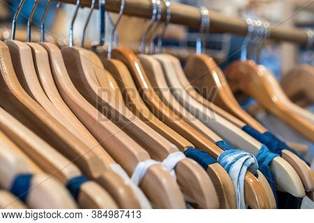 Clothes On Wooden Hangers In Shelf Fashion For Sale In Shopfront Store, Retail Background.
