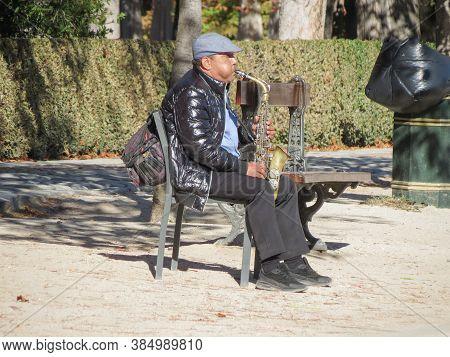 Madrid, Spain - Circa October 2017: Unidentified Street Musician Playing Alto Saxophone At Retiro Pa