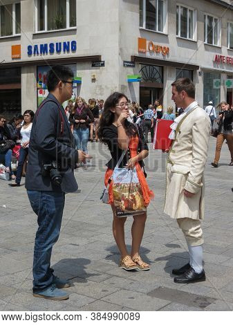 Vienna, Circa June 2013 - Mozart Man Trying To Sell  Concert Ticket To A Couple Of Asian Tourists In
