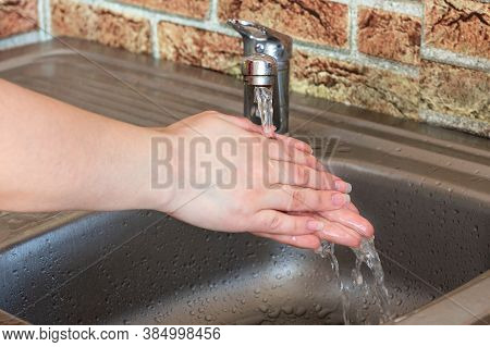 Caucasian Woman Wash Her Hands With The Water In The Metal Sink At Home. Bodycare And Health Protect