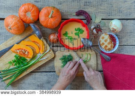 Pumpkin Soup On Wooden Table With Red Linen Cloth And Vintage Cutlery. Woman Hands Cutting Vegetable