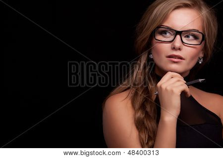 cheerful thinking or planning young business woman with pen, isolated on black background
