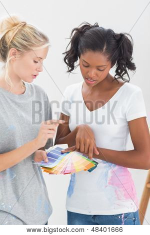 Young housemates choosing color for wall in new home