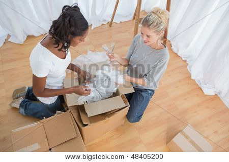 Young housemates unpacking boxes in new home and chatting together