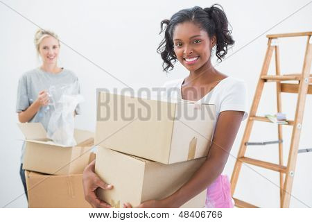 Smiling young housemates moving into new home and unpacking boxes