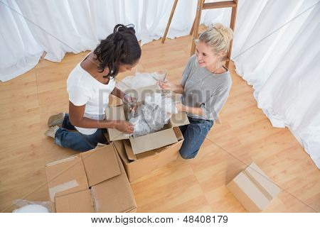 Young housemates unpacking in new home and chatting together