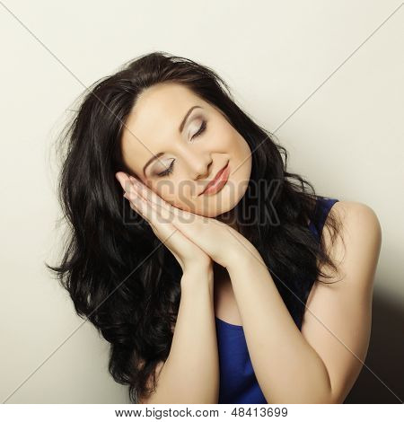 Portrait of young beautiful woman with eyes closed propping up her face against gray background.
