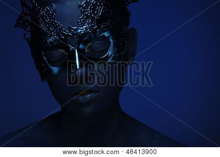 art photo of a beautiful woman with blue face with mask