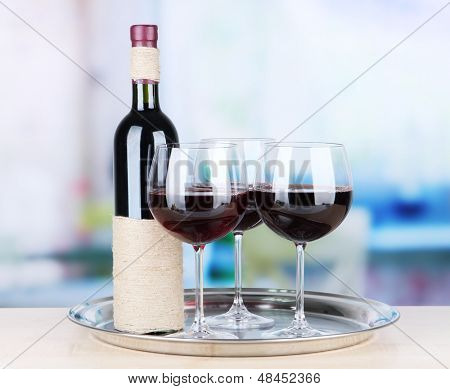 Wine glasses and bottle on bright background