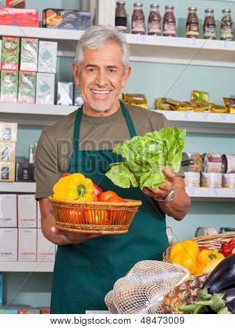 Happy senior salesman selling vegetables in grocery store