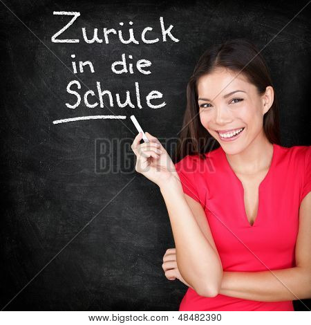 Zur�¼ck in die schule - German teacher Back to School written in German on blackboard by woman teacher holding chalk. Smiling happy woman teaching German language or university student back in college.