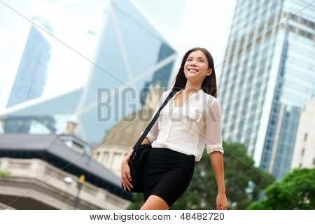 Asian Business woman walking outside in Hong Kong. Asian businesswoman office worker in downtown business district. Young multiracial Chinese Asian / Caucasian female professional in central Hong Kong