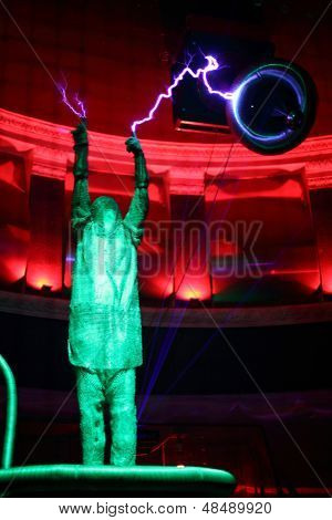 MOSCOW - FEBRUARY 8: Man in special clothes holds two lightnings at presentation of attraction Megavolt - master of lightning at VVC, on February 8, 2013 in Moscow, Russia.