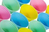 Cupcake baking cups in pastel colors isolated over white poster