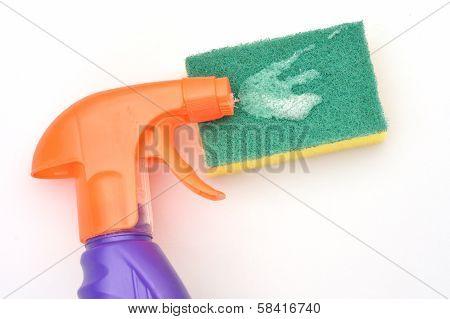 Orange spray bottle with green scourer