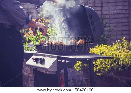 Man Cooking Meat On Barbecue Outdoors