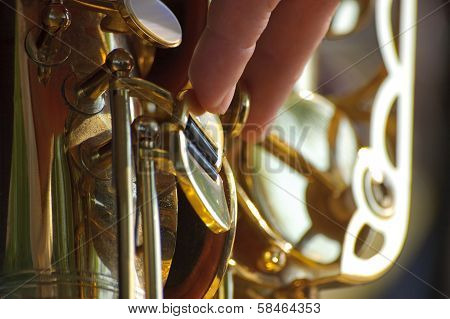 The player presses button on a saxophone