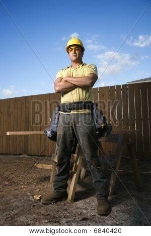 Mannelijke bouw werknemer Stands met gevouwen armen