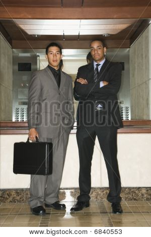 Two Businessmen Standing In Lobby