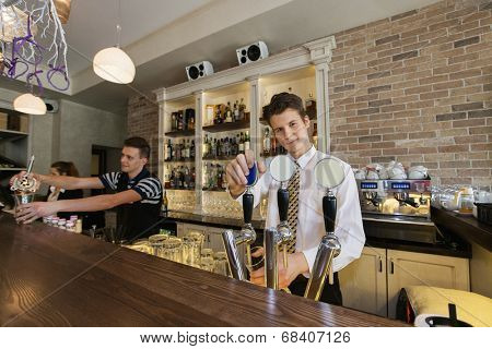Portrait of confident bartender at counter with coworkers in background