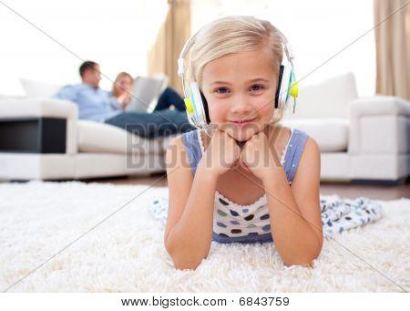 Smiling Little Girl Listening Music Lying On The Floor