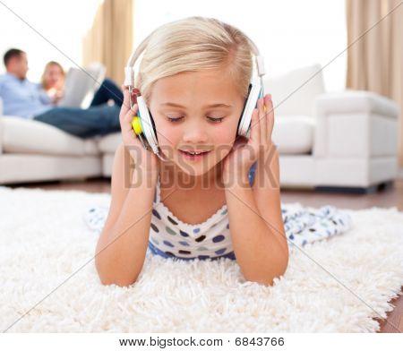 Cute Little Girl Listening Music Lying On The Floor