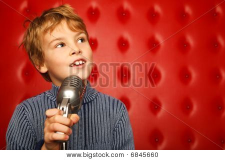 Singing boy with microphone on rack against red wall. Close up. Horizontal format.