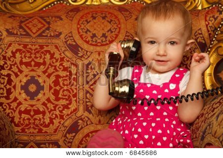 Little girl in red dress talking vintage phone. Interior in retro style. Horizontal format. Close up