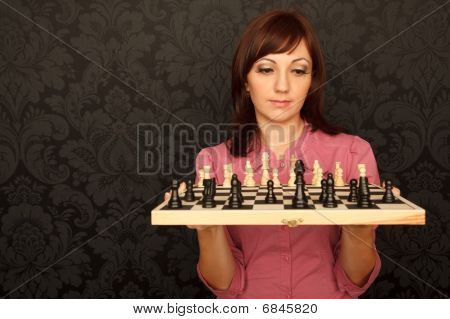 Portrait of girl in red shirt with chessboard against the wall with ornament