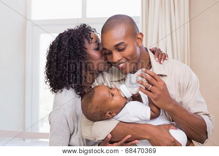 Happy parents feeding their baby boy a bottle at home in the bedroom