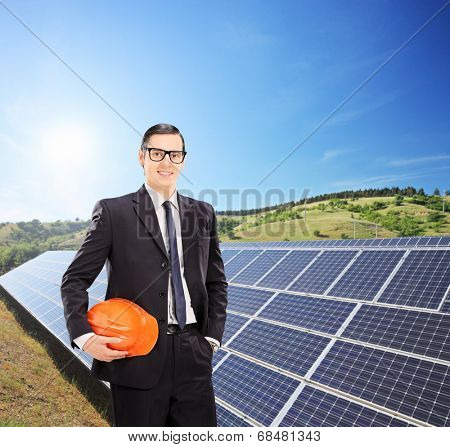 Young engineer standing in front of solar panels outdoors shot with tilt and shift lens