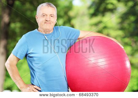 Mature sporty man holding a fitness ball in a park