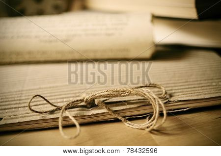 detail of an old notepad and some old rolled papers on a wooden table