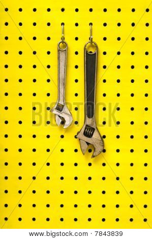 Two Wrenches Hang From Hooks On Yellow Pegboard