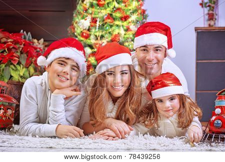 Happy family in Christmas eve, cheerful parents with two cute kids lying down on the floor near beautiful decorated Xmas tree