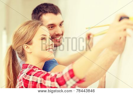 repair, building and home concept - smiling couple measuring wall