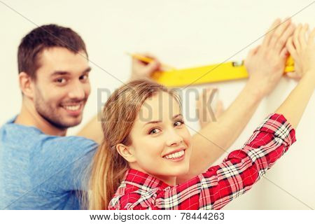 repair, building and home concept - smiling couple building new home using spirit level to measure